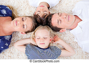 Relaxed family lying in circle on the wall-to-wall carpet at...
