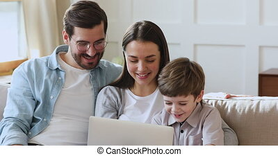 Relaxed family of three using laptop sit on sofa