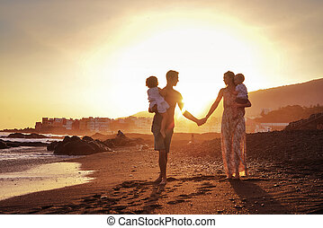 Relaxed family on tropical beach, beautiful sunset