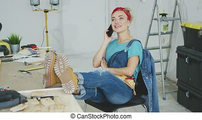 Relaxed female at workbench talking on smartphone - Cheerful...