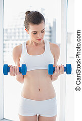Relaxed fit brown haired model in sportswear exercising with dumbells