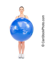 Relaxed fit woman holding exercise ball in front of her