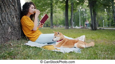 Relaxed girl drinking coffee and reading book in park...