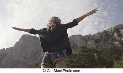 Relaxed girl hipster walking on the parapet along the cliffs...