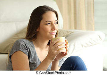 Relaxed girl thinking with a cup of coffee