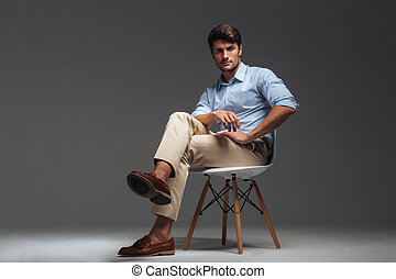 Relaxed handsome man in blue shirt sitting on the chair