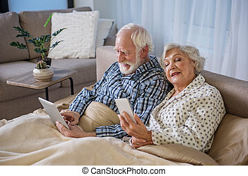 Relaxed husband and wife sitting in bed - Tranquil elderly...