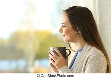 Relaxed lady holding coffee cup looks outside at home