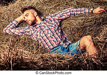 relaxed male - Handsome young man lying in haystack.