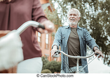 Relaxed male person enjoying walk on bicycles