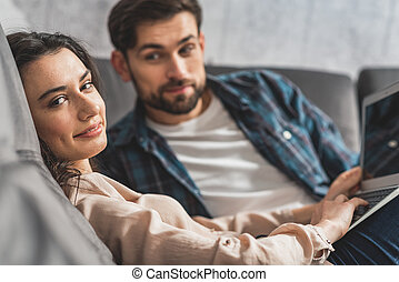 Relaxed man and woman resting on sofa