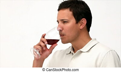 Relaxed man drinking red wine isolated on a white background