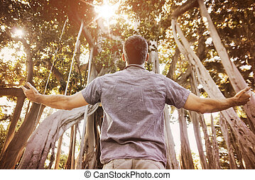 Relaxed man enjoying summer time in a tropical forest