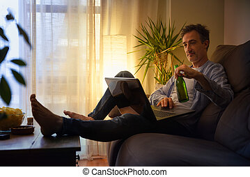 Relaxed man entertaining with a laptop at home with beer
