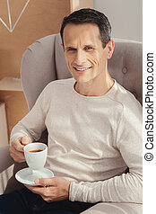 Relaxed man going to drink coffee
