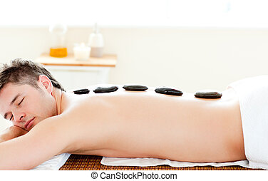 Relaxed man having hot stone on his back in a spa center