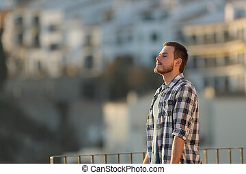 Relaxed man in a town breathing fresh air