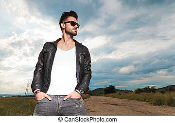 relaxed man in leather jacket standing with hands in pockets