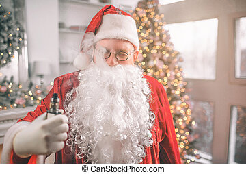 Relaxed man in Santa Claus costume stands and holds vape in hand. Smoke comes out of his mouth. He is relaxed.