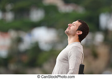 Relaxed man on a bench breathing fresh air