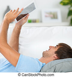 relaxed man reading an ebook