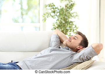 Relaxed man resting on a couch at home