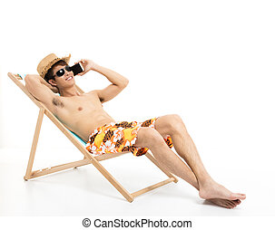 Relaxed man sitting in lounger chair and talking on the phone