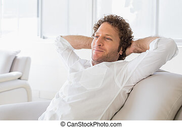 Relaxed man sitting with hands behind head at home