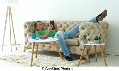 Relaxed man surfing on digital tablet at home