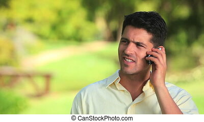 Relaxed man talking on phone outsid
