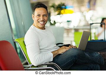 man using laptop at airport