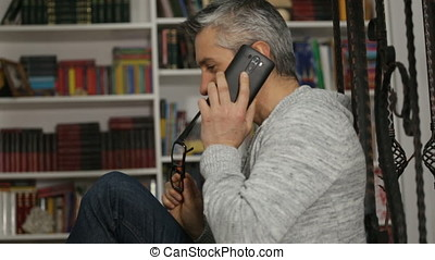 Relaxed man with eyeglasses holding digital tablet and talking on mobile phone against blurry bookshelves
