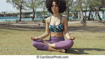Relaxed meditating woman on green lawn - Pretty slim black...