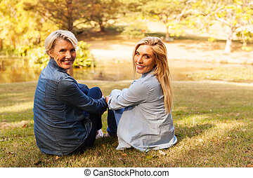 middle aged mother and daughter sitting outdoors