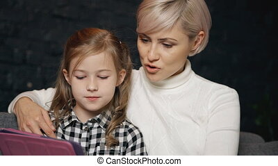 Relaxed mother using digital tablet with her charming...