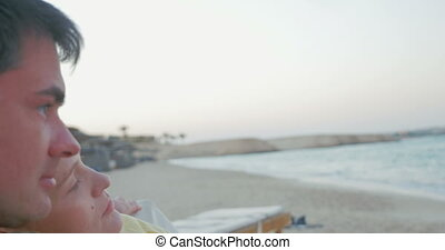 Relaxed parents and child with cell on the beach