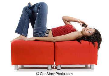 Relaxed Phone Call - An attractive young woman lies down to...