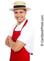 Relaxed portrait of smiling handsome chef posing with his...