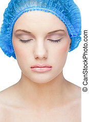 Relaxed pretty model on white background wearing blue surgical cap