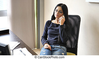 Relaxed pretty young businesswoman at desk on phone