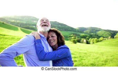 Relaxed senior couple hugging outside in spring nature. -...