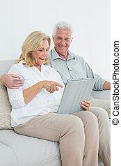Relaxed senior couple using digital tablet on sofa