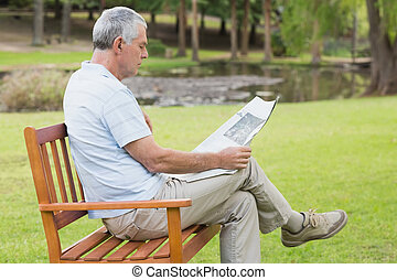 Relaxed senior man reading newspaper at park