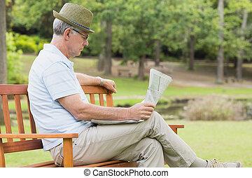 Relaxed senior man reading newspaper