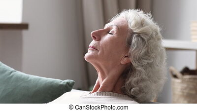 Closeup side view of serene calm elder woman resting meditating on sofa. Relaxed senior 70 years old lady takes deep breath of fresh air at home. Healthy grandma doing breathing exercise in living room