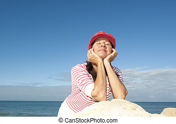 Relaxed senior woman ocean background