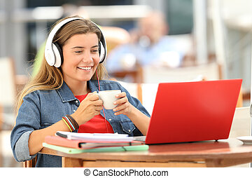 Relaxed student watching media in a laptop in a bar