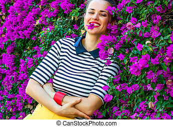 relaxed stylish woman in front of colorful magenta flowers...