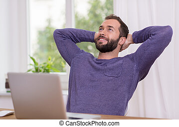Relaxed successful bearded man sitting at his desk with his...
