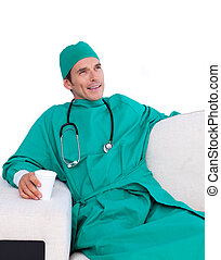 Relaxed surgeon drinking coffee in the staff room against a...